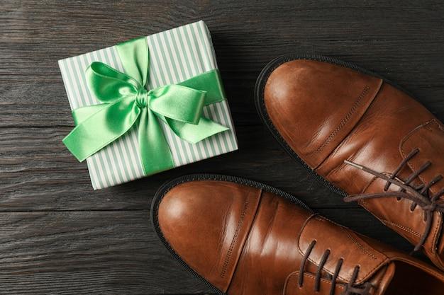 Caixa de presente com fita verde e sapatos de couro marrom com fundo de madeira, espaço para texto e vista superior