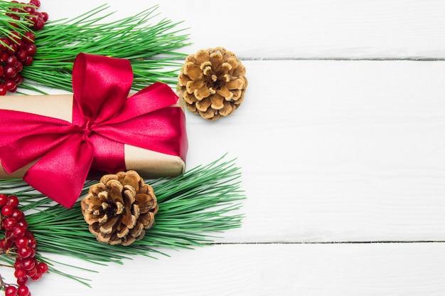 Caixa de presente com fita vermelha, arco e galho de árvore de natal com cone na superfície vintage de madeira branca