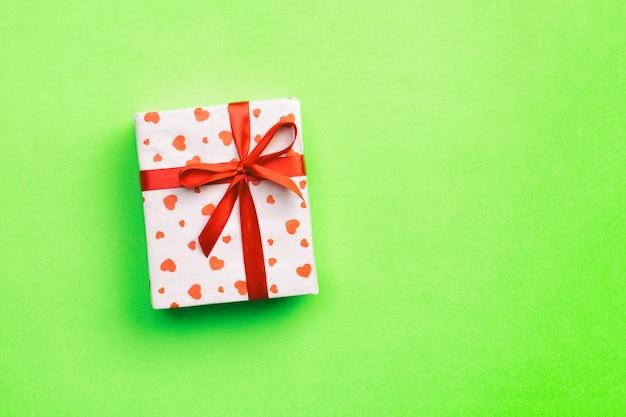 Caixa de presente com fita vermelha e coração em verde