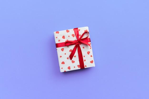 Caixa de presente com fita vermelha e coração no fundo roxo