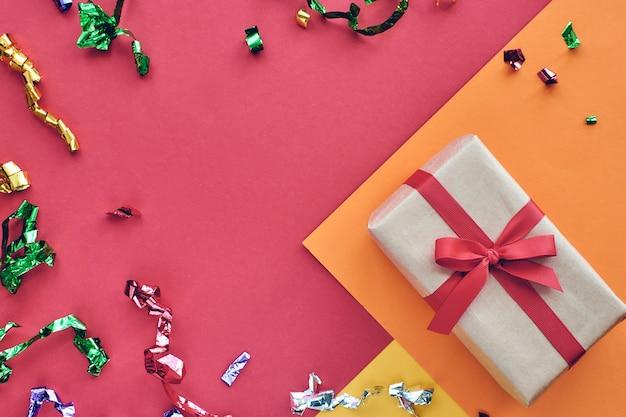 Caixa de presente com fita vermelha e enfeites de confete em fundo colorido de papel pastel