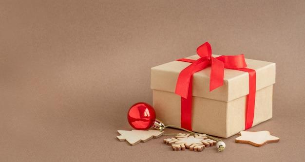 Caixa de presente com fita vermelha e enfeites de natal em fundo marrom