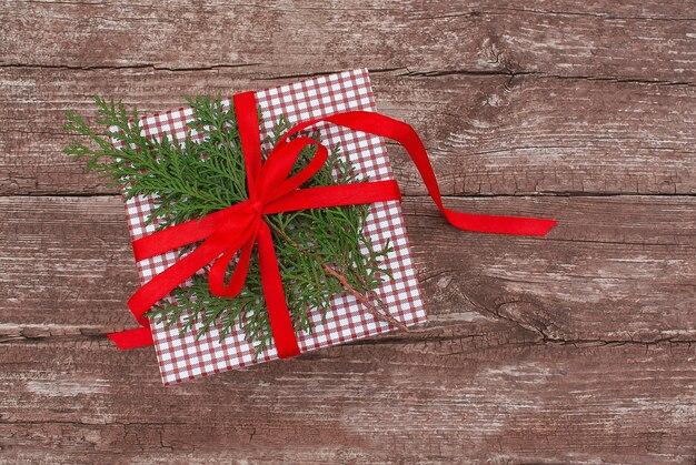 Caixa de presente com fita vermelha e raminho de árvore conífera na velha mesa de madeira