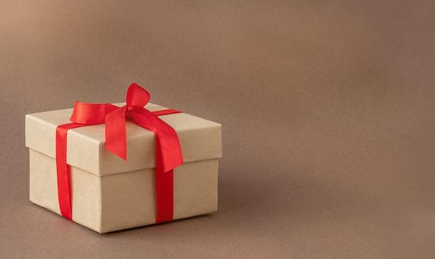 Caixa de presente com fita vermelha em fundo marrom