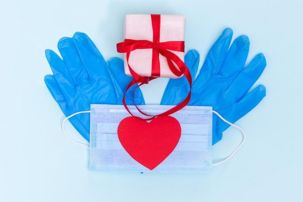 Caixa de presente com fita vermelha, luvas de proteção azuis e coração de amor de papel vermelho em uma máscara de proteção azul