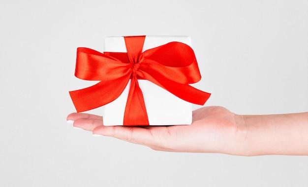 Caixa de presente com fita vermelha na mão na mesa branca para o dia dos namorados.