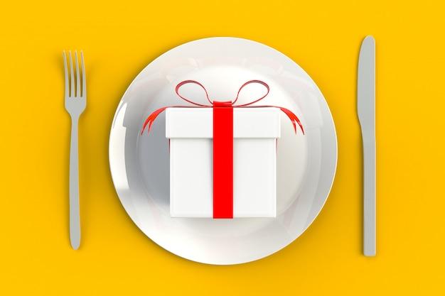 Caixa de presente com fita vermelha no prato, faca e garfo amarelo
