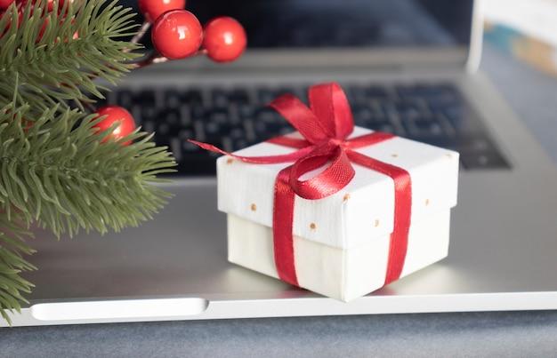 Caixa de presente com fita vermelha no teclado preto do laptop