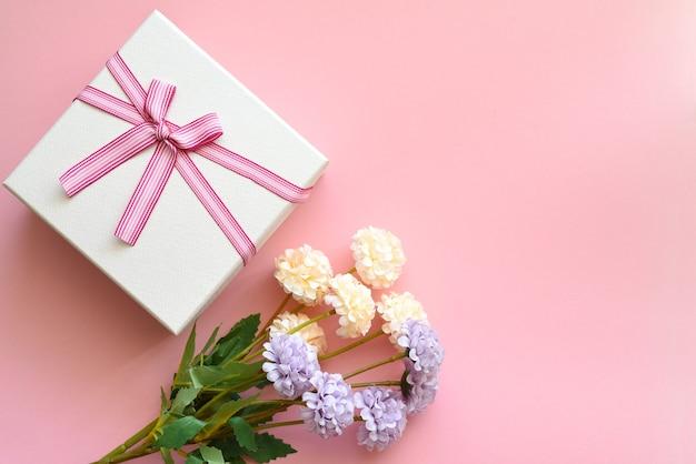 Caixa de presente com flores em uma parede rosa