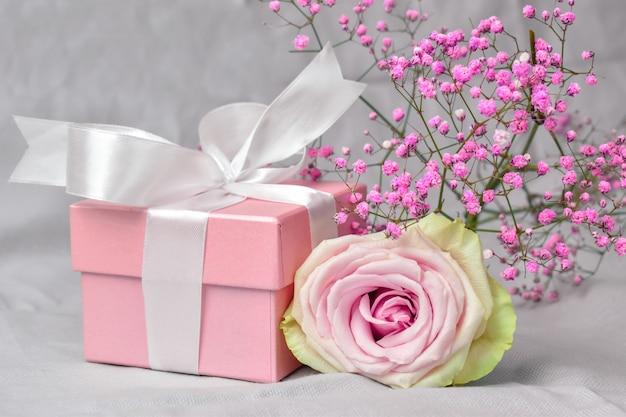Caixa de presente com flores no fundo rosa do dia dos namorados.