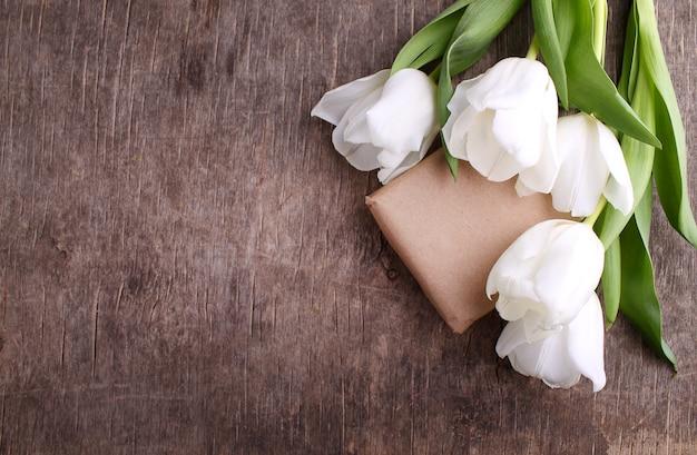 Caixa de presente com flores (tulipas brancas) sobre fundo de madeira rústica