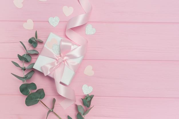 Caixa de presente com folhas de eucalipto e confete de corações de papel Foto Premium