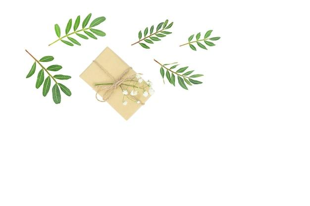 Caixa de presente com folhas verdes isoladas em branco
