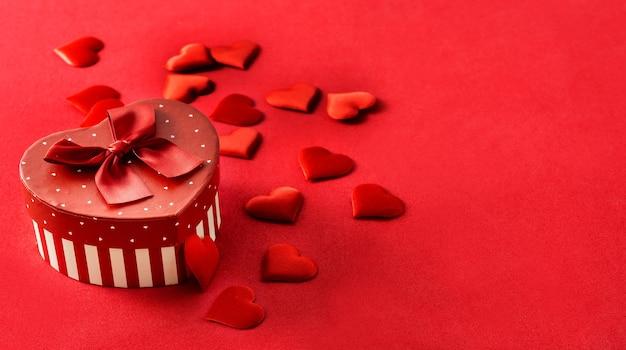 Caixa de presente com forma de coração e corações em fundo vermelho.