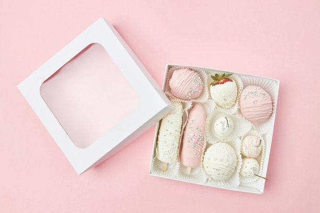 Caixa de presente com frutas maduras, cobertas com chocolate branco e rosa, encontra-se em um fundo rosa