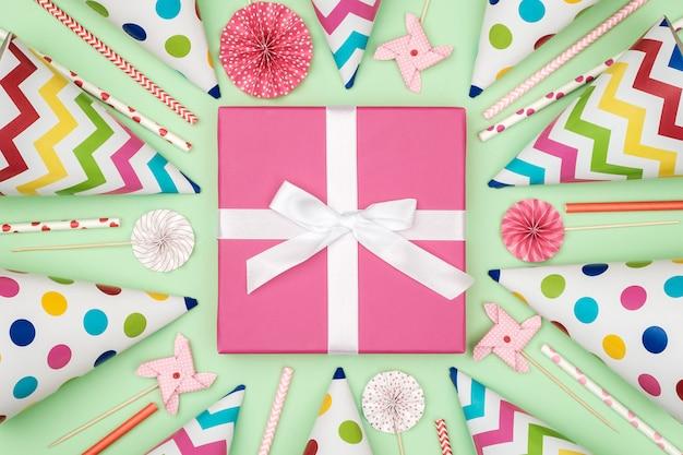 Caixa de presente com itens de festa em fundo colorido