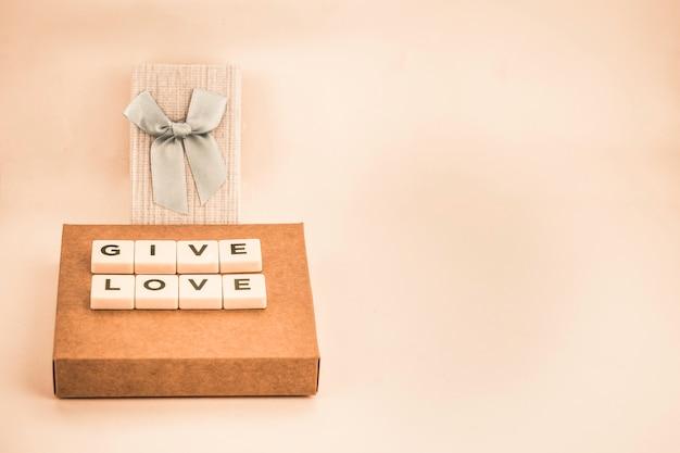 Caixa de presente com laço azul e a frase dar amor com espaço de cópia