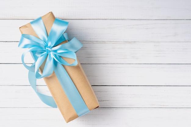 Caixa de presente com laço azul em uma superfície de madeira branca com espaço de cópia