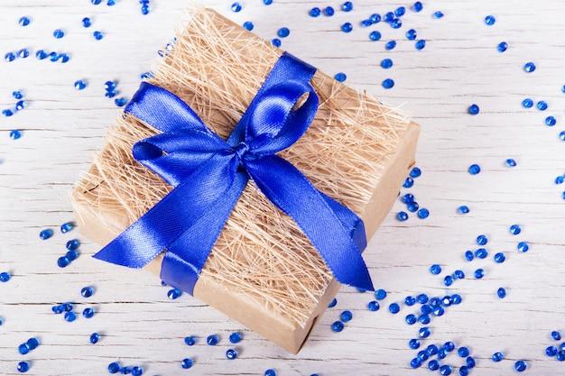 Caixa de presente com laço azul sobre um fundo branco com brilhos