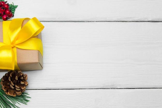 Caixa de presente com laço de fita amarela e galho de árvore de natal com cone na superfície vintage de madeira branca