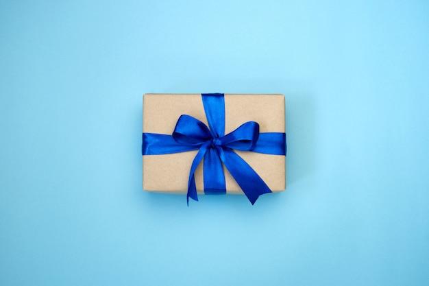Caixa de presente com laço de fita azul, embrulhado em papel ofício sobre fundo azul.