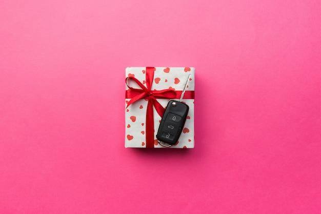 Caixa de presente com laço de fita vermelha, chave de coração e carro em fundo colorido
