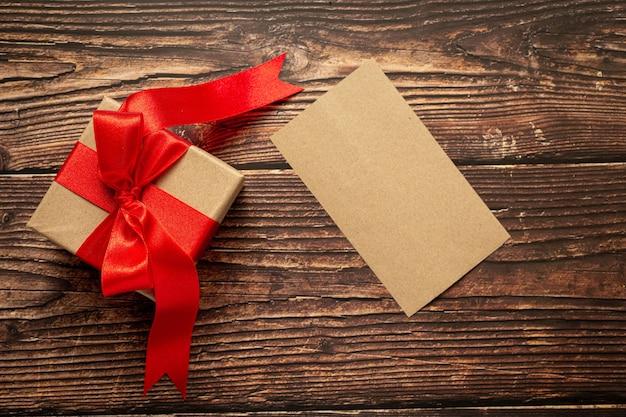 Caixa de presente com laço de fita vermelha em fundo de madeira