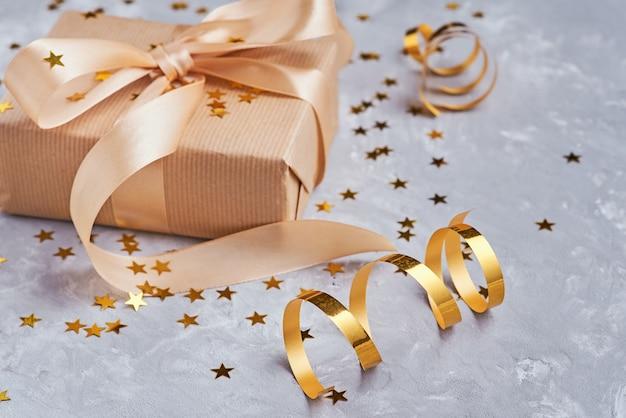 Caixa de presente com laço dourado e confetes, close-up
