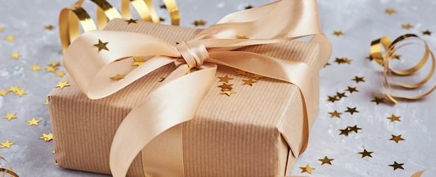 Caixa de presente com laço dourado e confetes, web banner