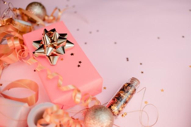 Caixa de presente com laço dourado em fundo preto com decoração e brilhos