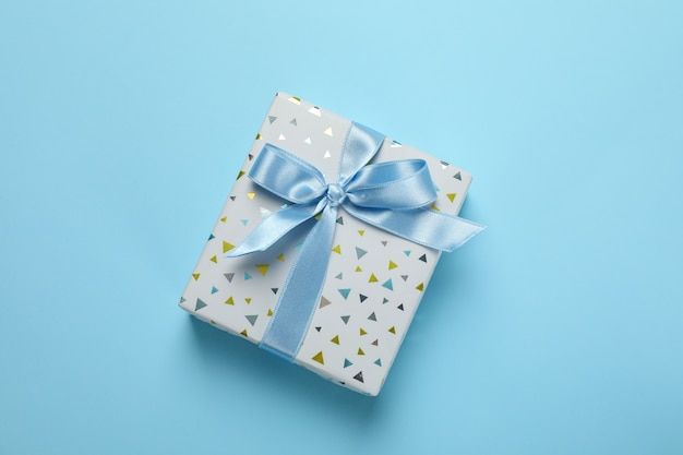 Caixa de presente com laço em fundo azul, espaço para texto