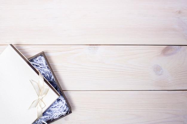 Caixa de presente com laço em fundo de madeira