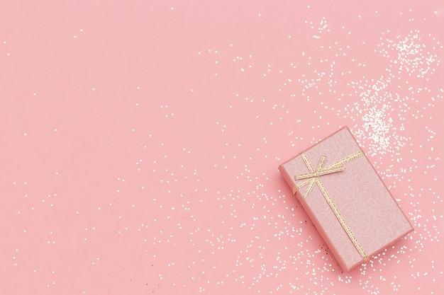 Caixa de presente com laço no canto no fundo rosa pastel em estilo minimalista