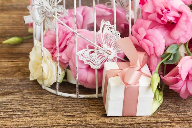 Caixa de presente com laço rosa e buquê de rosas frescas e flores de eustoma