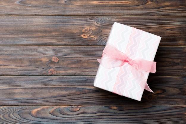 Caixa de presente com laço rosa na mesa de madeira escura