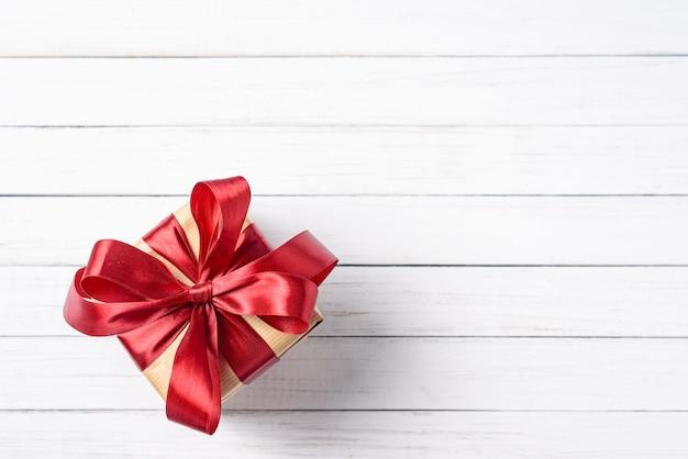 Caixa de presente com laço vermelho sobre um fundo branco de madeira com espaço de cópia