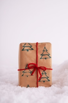 Caixa de presente com o padrão de árvores de natal e uma fita vermelha na neve