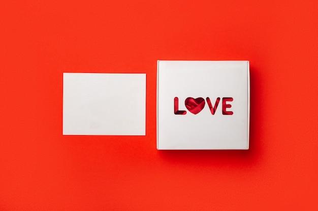Caixa de presente com o texto amor e cartão em um fundo vermelho. composição do dia dos namorados. bandeira. camada plana, vista superior.