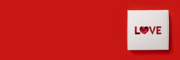 Caixa de presente com o texto amor sobre um fundo vermelho. composição do dia dos namorados. bandeira. camada plana, vista superior.