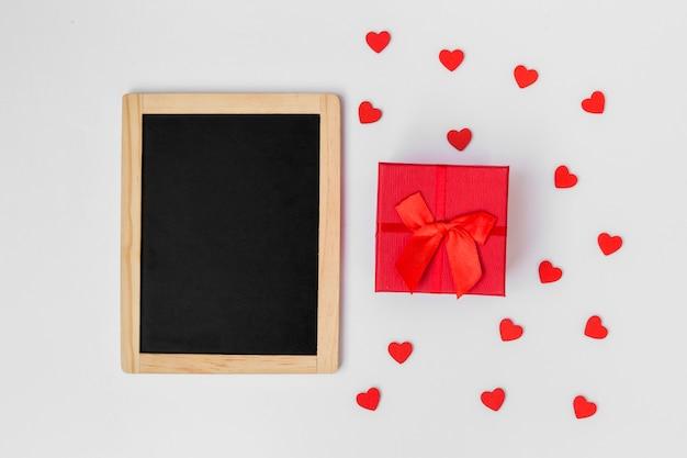 Caixa de presente com pequenos corações e lousa na mesa