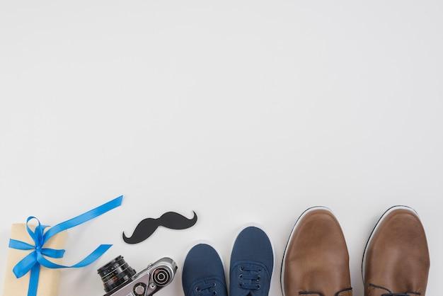 Caixa de presente com sapatos de homem, câmera e bigode
