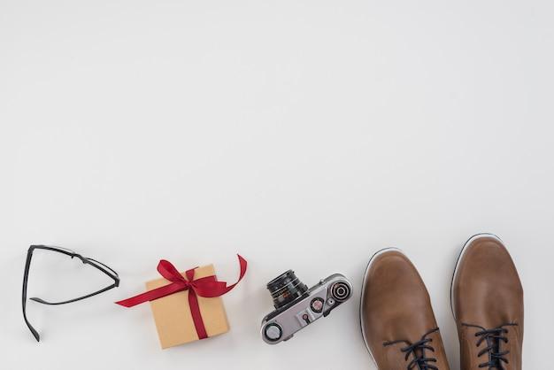 Caixa de presente com sapatos de homem e câmera