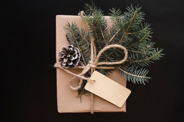 Caixa de presente com senão, etiqueta e galhos de pinheiro