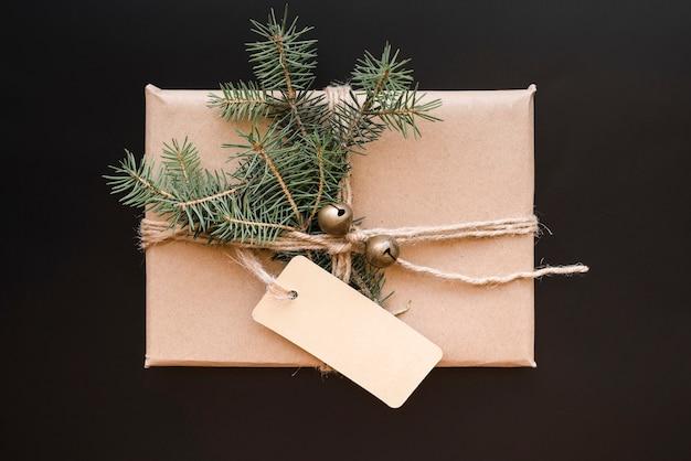 Caixa de presente com senão, tag e galhos de coníferas