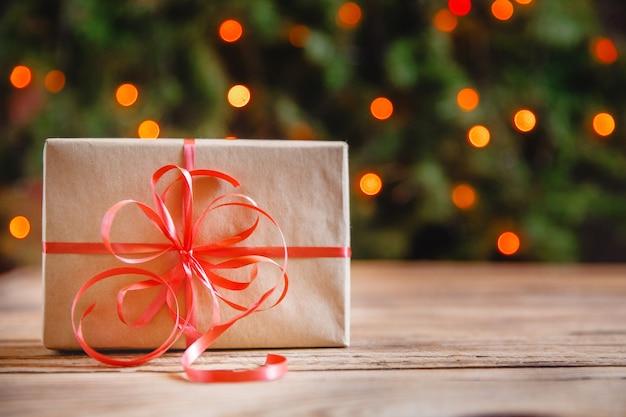 Caixa de presente com um grande laço vermelho contra um bokeh de fundo de luzes cintilantes de festa. presente de natal.