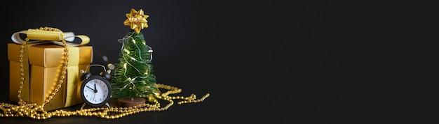 Caixa de presente com um laço dourado. despertador branco e uma pequena árvore de natal em um fundo preto.
