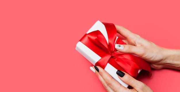 Caixa de presente com um laço nas mãos de uma mulher em uma superfície vermelha