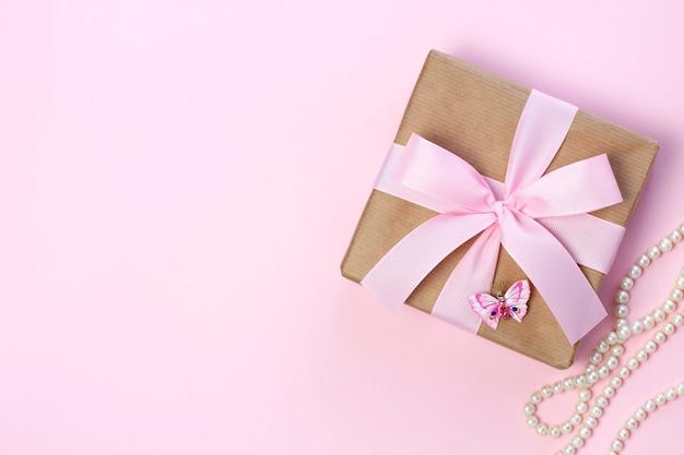 Caixa de presente com um laço rosa e pérola em um fundo rosa pastel. estilo liso leigo.