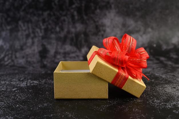Caixa de presente com um laço vermelho amarrado e aberto.