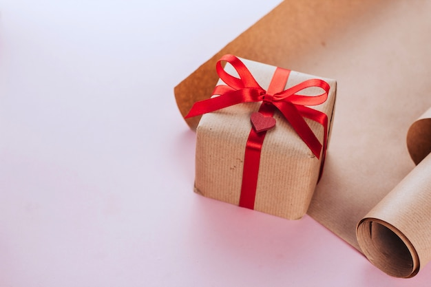 Caixa de presente com um laço vermelho envolto em espaço de cópia em papel marrom. presente de dia dos namorados. rolo de papel de embrulho marrom